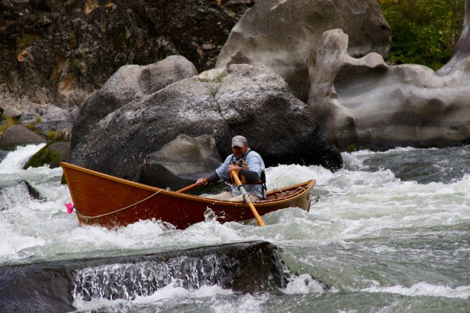 Greg Hatten steers his wooden drift boat through the rapids on the Rogue River.
