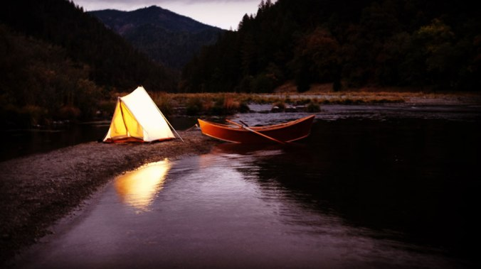 An evening outdoors shot, with a lit canvas tent, and an empty wooden drift boat by the shore of a small river.
