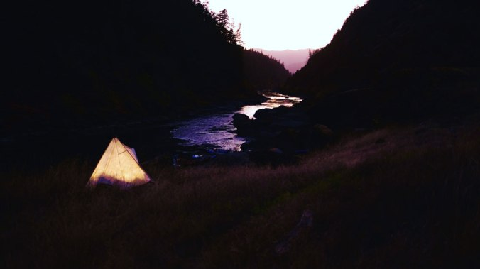 A lit canvas tent glows beside a river in Oregon, as the sun sets.