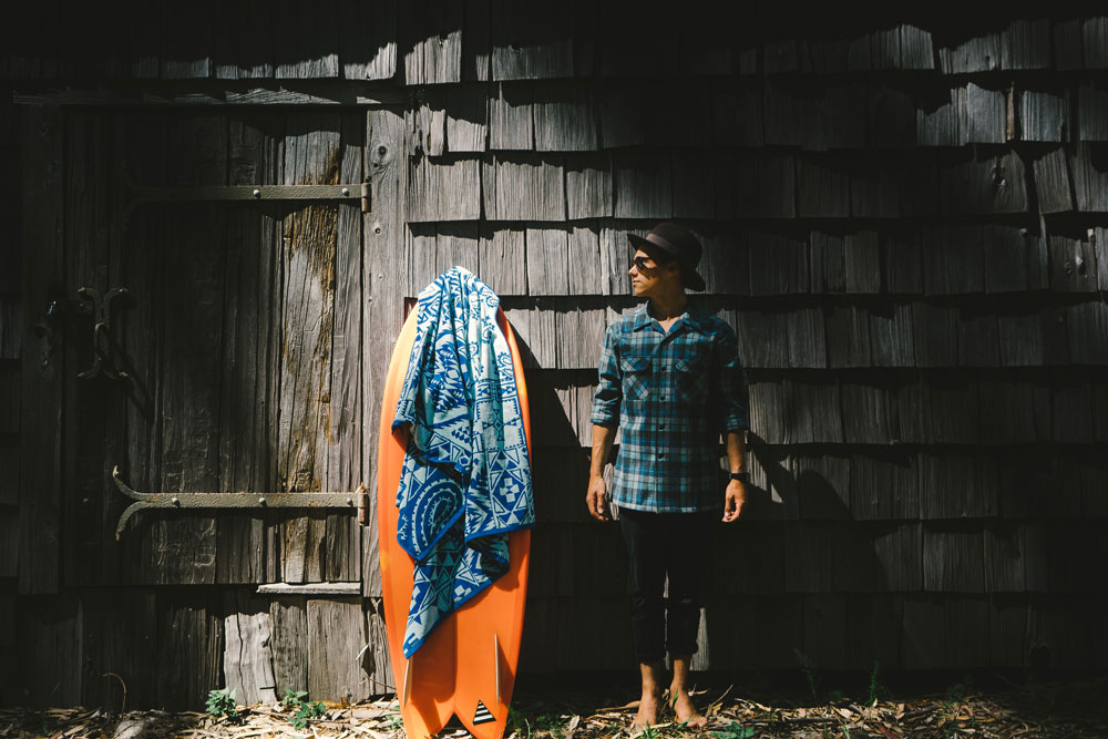 A young man stands next to an orange surfboard in front of a shingled wall. He is wearing a Pendleton Board Shirt in the Original Surf Plaid made famous by The Beach Boys.