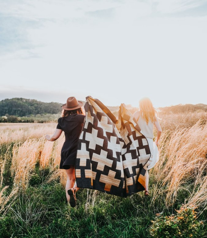 Two young women run away from the camera through a field with tall grasses in the sunshine. They are holding a pendleton Compass point blanket between them as they run.