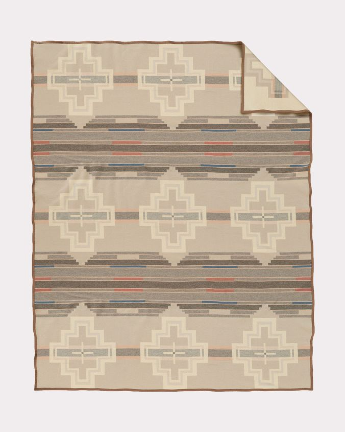 The Santa Clara blanket by Pendleton is a geometric pattern in shades of creme, taupe and beige, with mall accents of rust and marine blue.