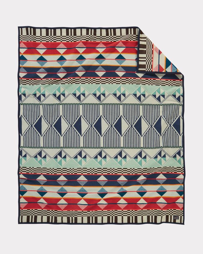 The Southern Highlands blanket by Pendleton is a geometric pattern in pale green, navy blue, rust red and beige.