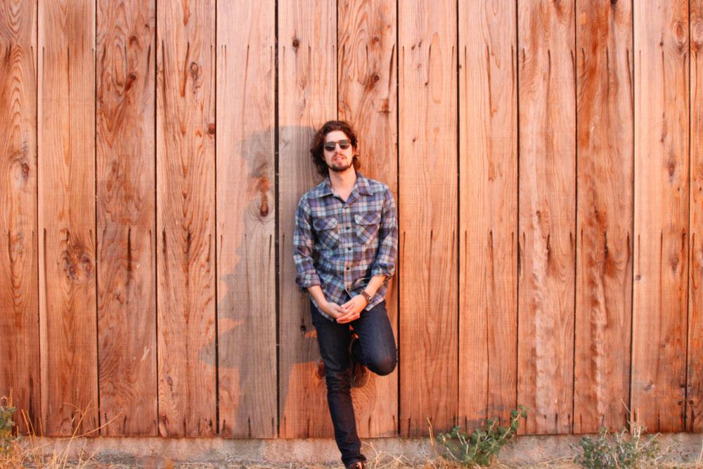 Musician Ben Jaffe leans against a cedarwood wall. He is wearing a Pendleton Board Shirt in Original Surf Plaid.