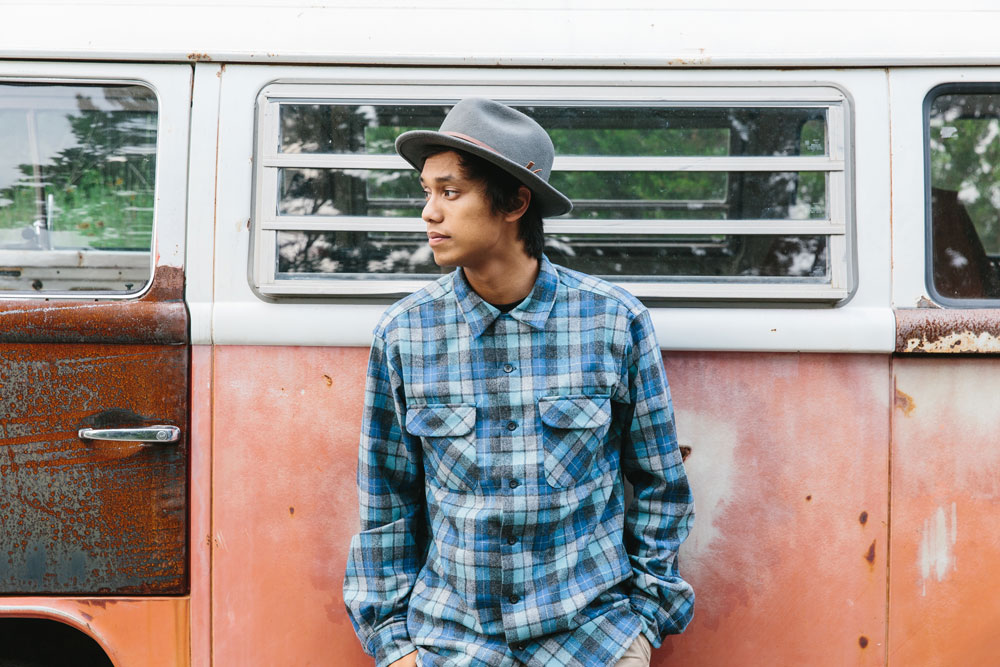 A young man leans against a rusted orange camper. he is wearing a Pendleton Board Shirt in Original Surf Plaid.