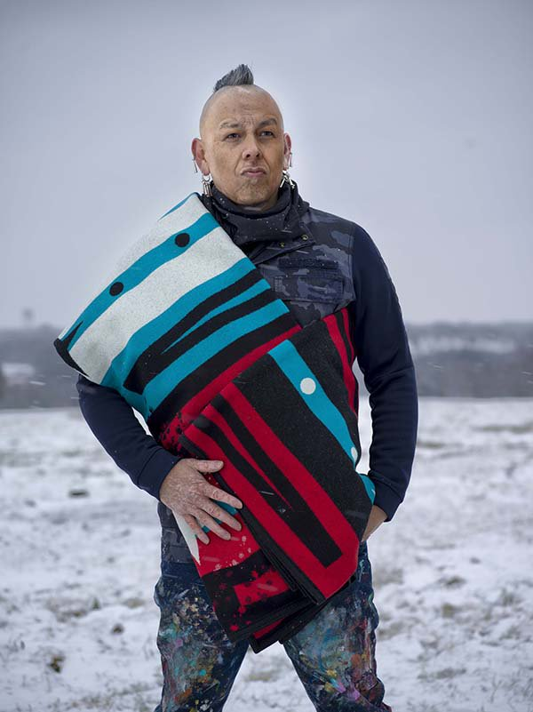 Artist Bunky Echo-Hawk stands in a field, wrapped in the Pathway blanket he designed for Pendleton, for the American Indian College Fund. Photo by Ryan Redcorn.