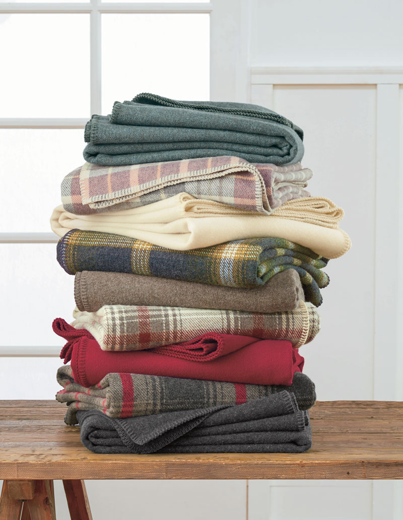 A stack of folded Pendleton Eco-Wise Wool bed blankets on a wooden table.