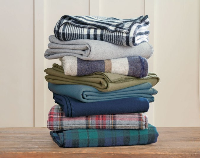 Another stack of folded Pendleton Eco-Wise Wool bed blankets on a wooden table.