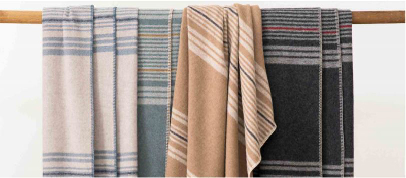 Four Pendleton Eco-Wise Wool striped throws draped across a wooden dowel.