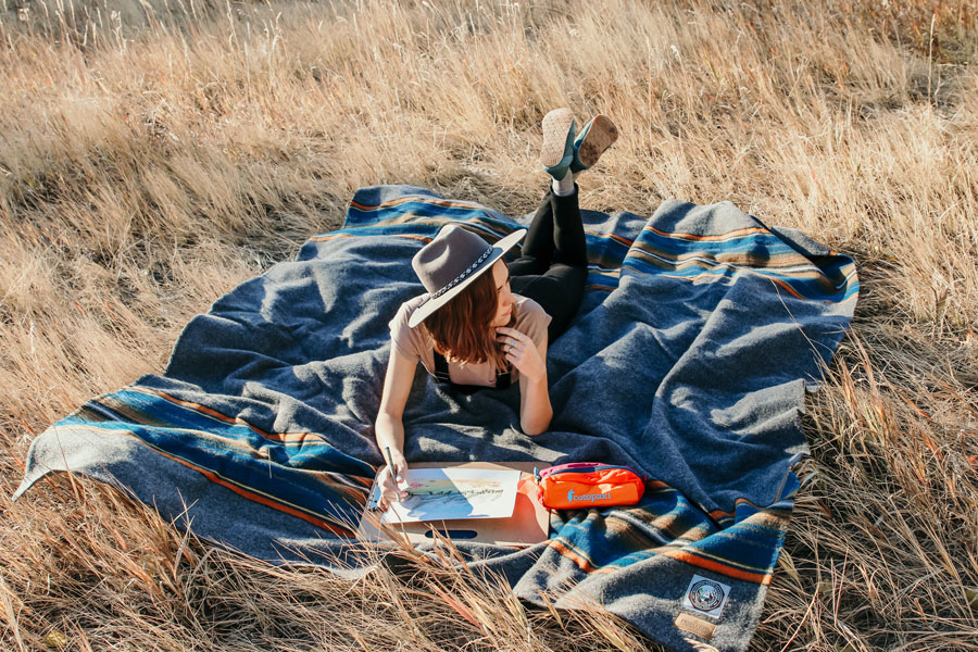 A young woman lays on her stomach on a Pendleton Olympic National park blanket, in a field of tall, dry grass. She is painting a watercolor.