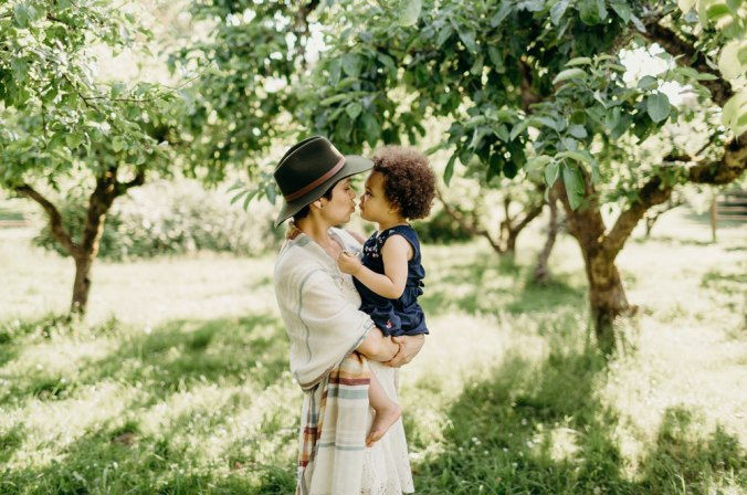 A mother wearing a Pendleton scarf and hat, with her 2 year old daughter in a sun dappled orchard