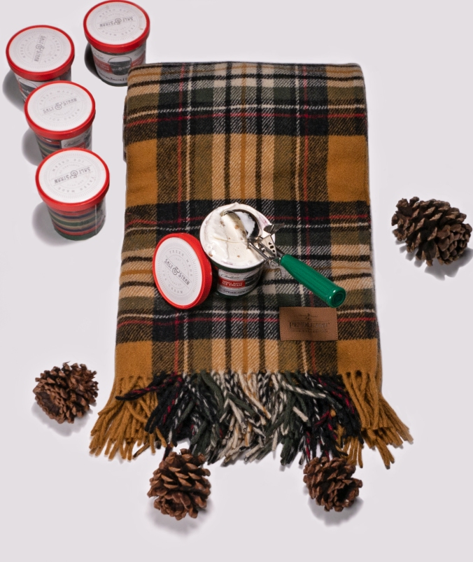 A folded Pendleton Motor Robe in a plaid of gold, black, tan, white and red sits on a white background, next to four pinecones. Four slosed pint containers of Salt & Strwa ice cream are to the upper left of the blankets, and one open pint of ice cream sits on the throw, with a green-handled ice cream scooper in the ice cream.