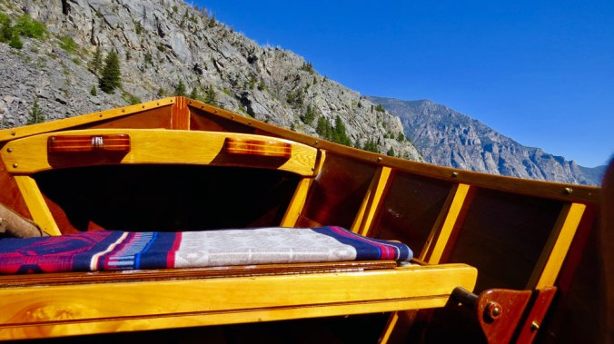 Photo taken inside a handmade wooden drift boat, showing the Pendleton Bighorn blanket on the boat's seat, against a backdrop of Montana mountains.