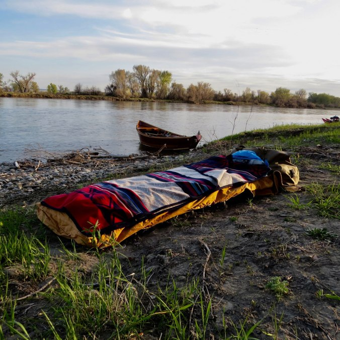 A camp cot set up on the banks of a river, with a wooden boat on the river, and a Pendleton Bighorn blanket on the bed.