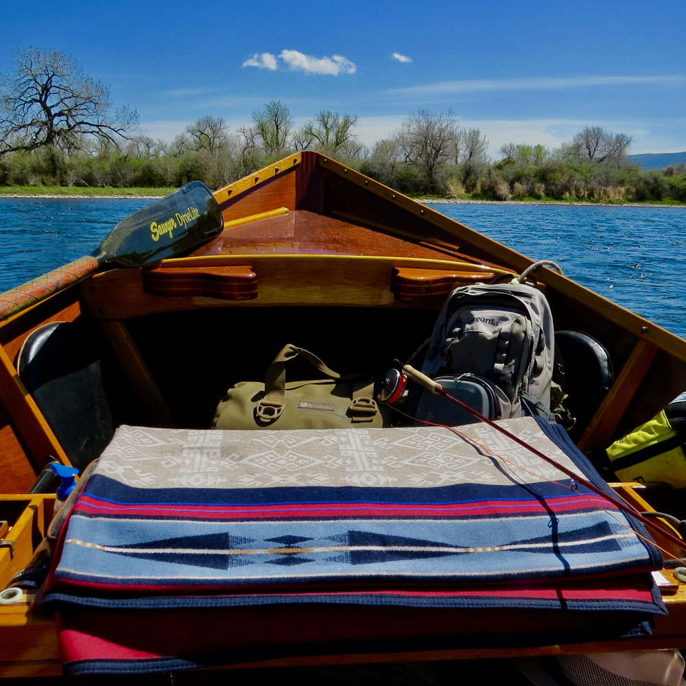 Photo taken from within a hand-built wooden drift boat, showing a folded Pendleton Bighorn blanket on the seat, and gear packed below the boat's prow, which is poised above the waters of Montana's Bighorn river.