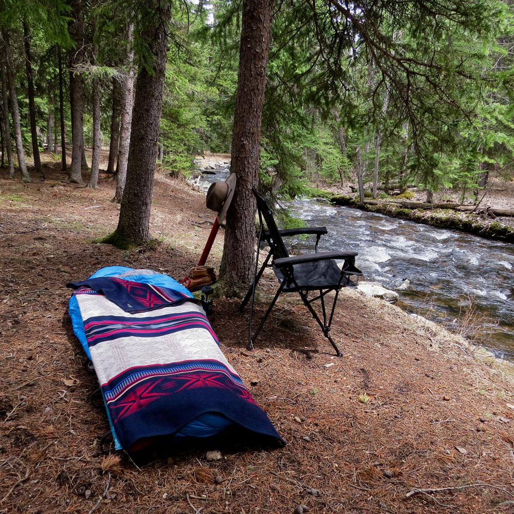 A camp cot and folding camp chair on the banks of a rushing river, under evergreen trees. I Pendleton Bighorn blanket is on the cot.
