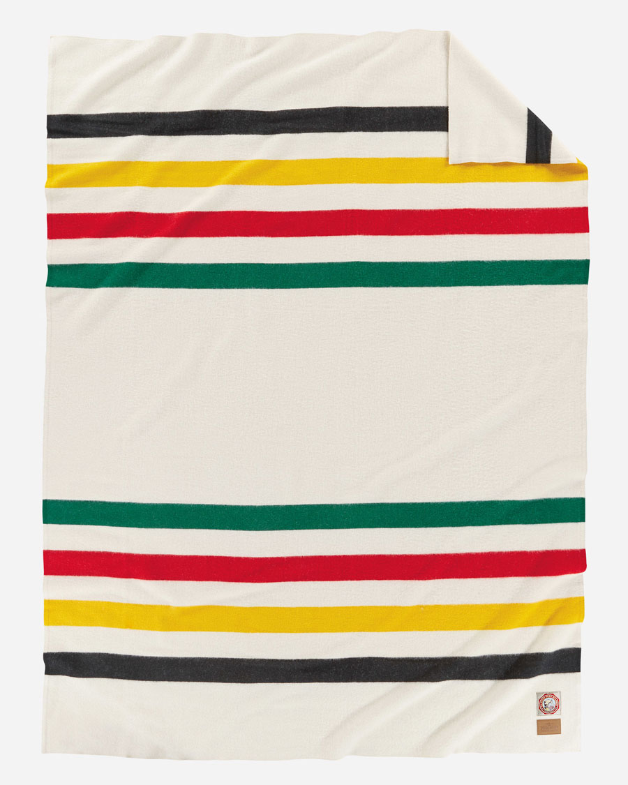 The Glacier National Park blanket, by Pendleton. A white background with a stripe of black, yellow, red and green at each end.
