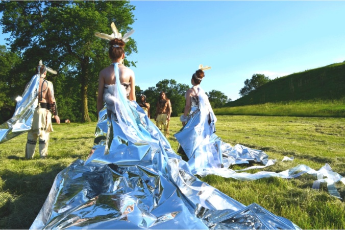 A group of models stand in a meadow, modeling wearable artworks that incorporate long sheets of shining silver Mylar, by artist Wendy Ponca.