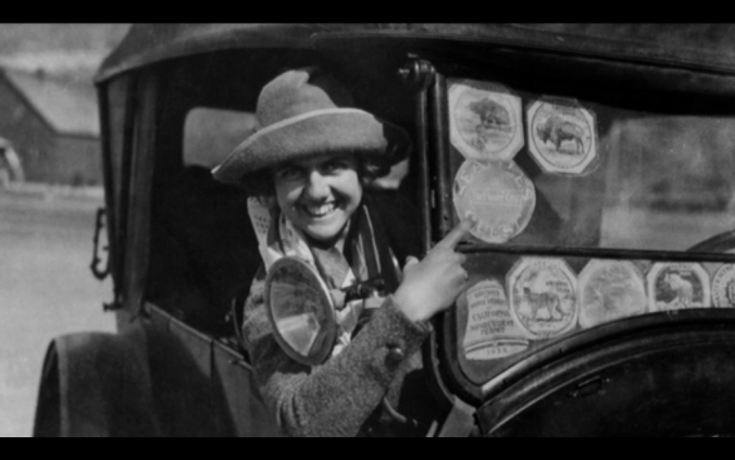 In a vintage photograph from the 1920s, a smiling woman in a Model T Ford points at her windshield to show off her National Park stickers.