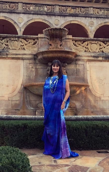 Artist Wendy Ponca poses before a stone fountain in one of her own flowing creations, a gown in shades of royal blue and purple.