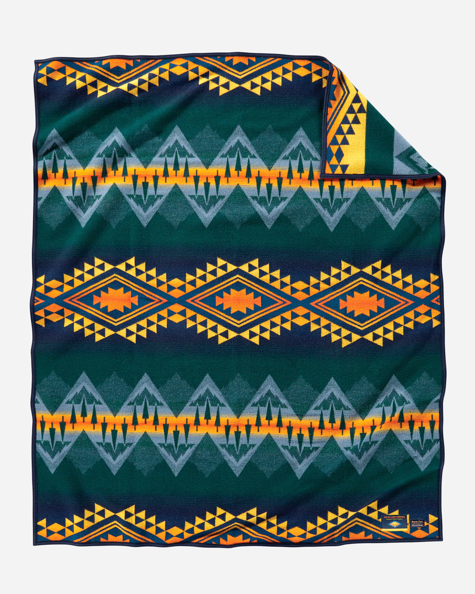 The Pendleton Wildland Heroes blanket shows bands of geometric designs that also include evergreen trees, with a dark forest green background, light blue trangles to symbolize water, and yellow and orange accents that represent the threat of wildfires.