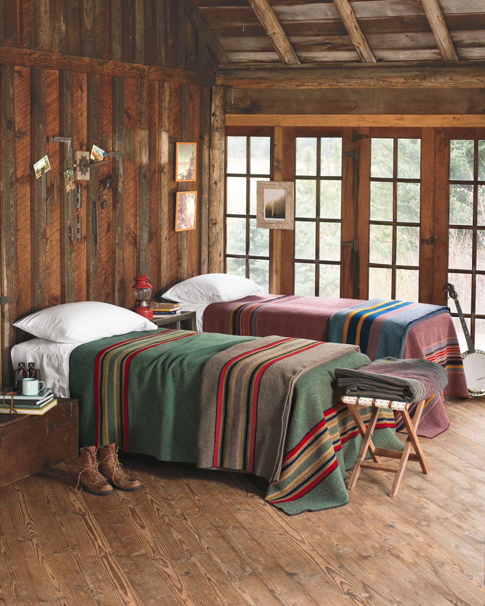 two beds in a log building by a window. Beds are covered with Pendleton Yakima Camp blankets, one green with stripes, one red with stripes.