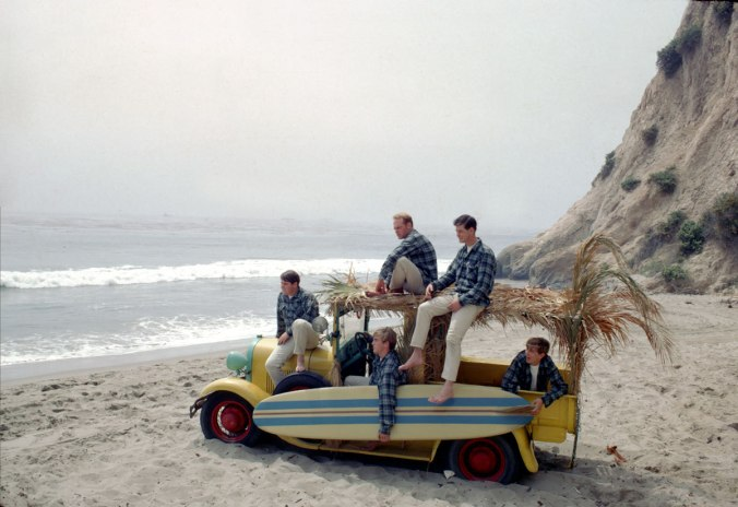 The Beach Boys in their Pendleton shirts, posing with a surfboard and palm-bedecked beach wagon on the California coast.