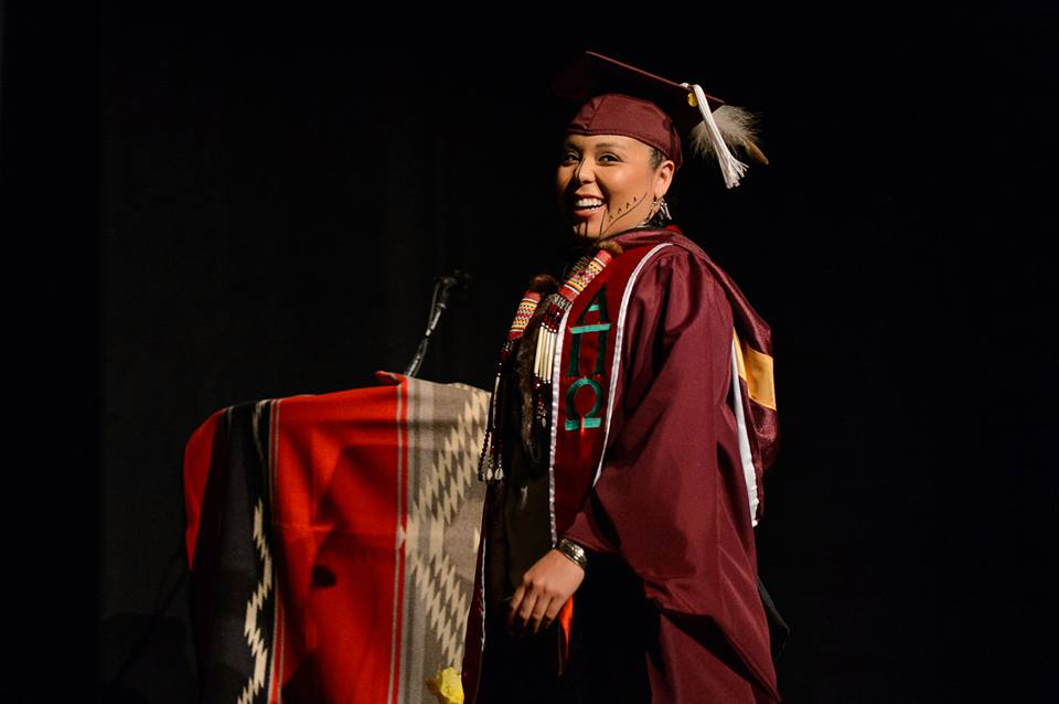 A young Native American woman in a maroon graduation robe and gown stands by a podium draped with a Pendleton Water blanket.