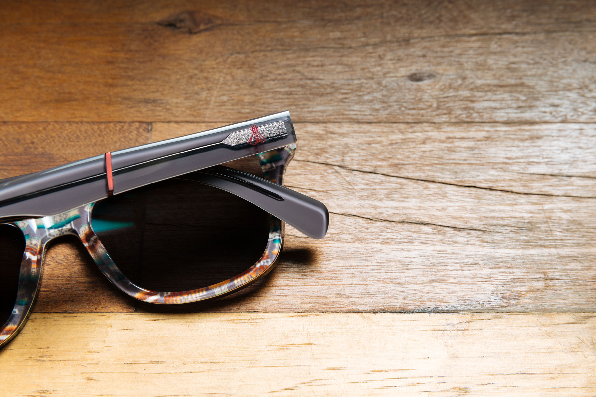 A pair of Pendleton x Shwood sunglasses sits on a wood table. You can see the details of the branding in this shot, including the Chief Joseph pattern and a small teepee in red on the eyeglass stem.