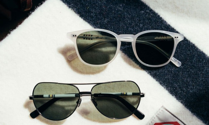 Two pairs of Pendleton x Shwood sunglasses sit on a folded Glacier National Park blanket by Pendleton.