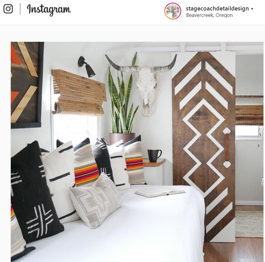The interior of a restored vintage Airstream trailer holds a daybed dressed with throw pillows made of Pendleton Sunbrella fabrics.