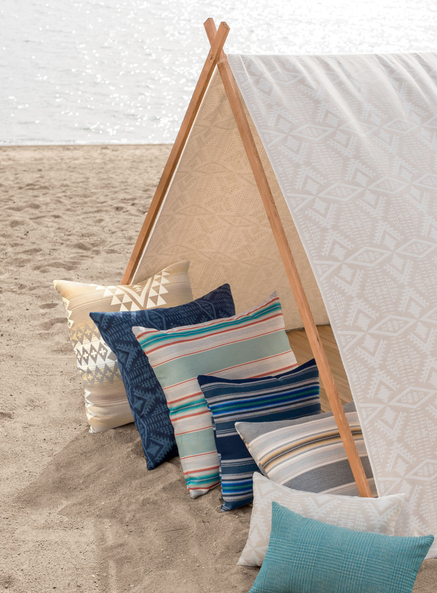 A sandy beach and a tent made of Pendleton by Sunbrella outdoor fabrics, holding a group of throw pillows.
