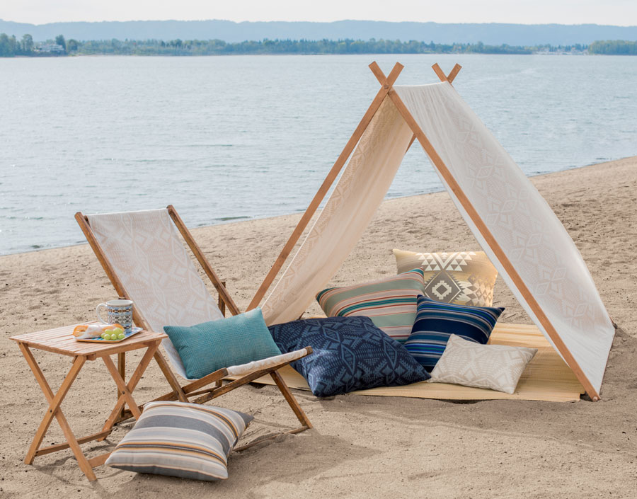 A sandy beach, with a folding chair, seven throw pillows, and tent made of Pendleton by Sunbrella fabrics.