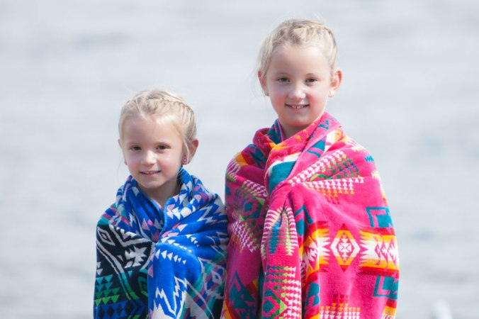 Two little girls who look like sisters, with blond braided hair, stand in front of water, wrapped in Pendleton beach towels.