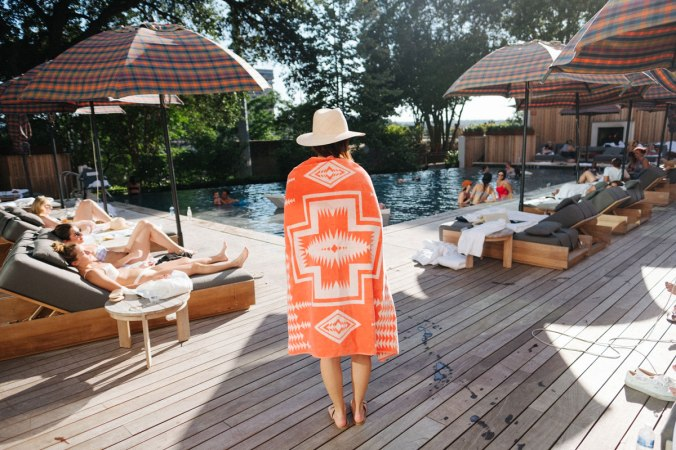 A young woman wrapped in an orange Pendleton beach towel stands on a wooden deck, looking at a swimming pool. Her back is to the camera and she is wearing a straw hat.