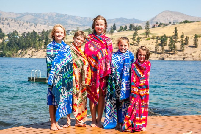 A group of children stand on a dock by a lake, all wrapped in colorful patterned Pendleton beach towels.