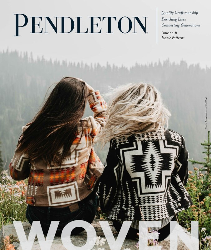 two women with long hair sit on a hilltop wearing Pendleton jackets