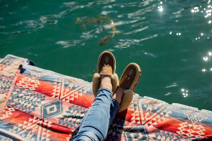 A Pendleton Canyonland beach towel spread on a lake. A woman's lower legs and feet, clad in jeans and beautiful Manitobah moccassins, extend over green lake water that shines with pinpoints of sunlight.