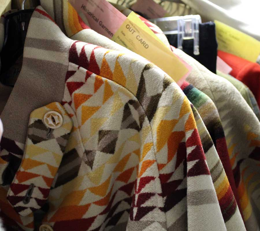 """A group of vintage Pendleton blanket coats hanging together in the Pendleton archives. Yellow and pink pieces of paper calle d""""out cards"""" are interspersed, showing where garments have been checked out of the archives for design inspiration."""