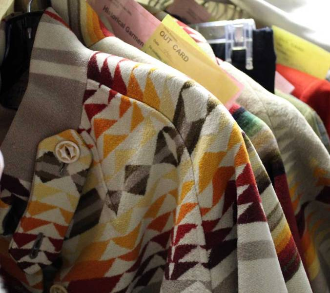 "A group of vintage Pendleton blanket coats hanging together in the Pendleton archives. Yellow and pink pieces of paper calle d""out cards"" are interspersed, showing where garments have been checked out of the archives for design inspiration."