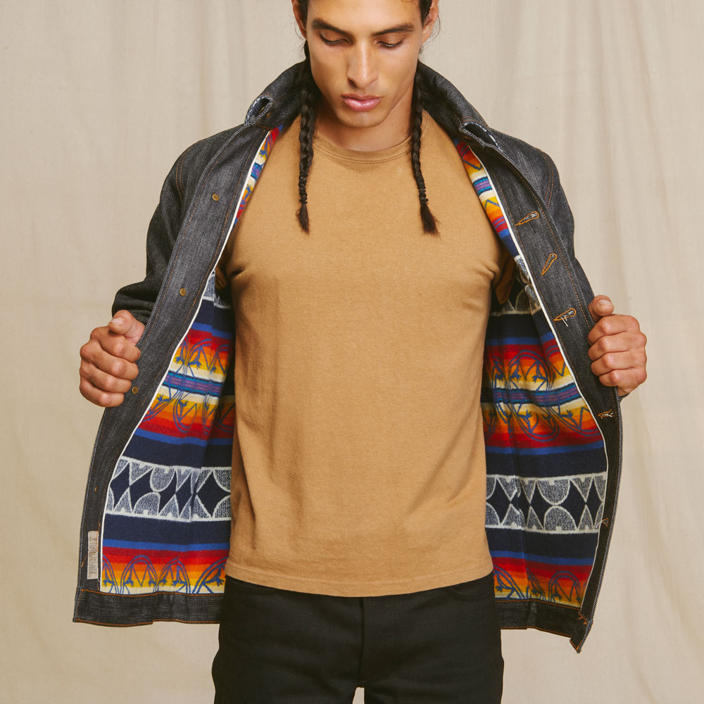 A Native American model stands facing the camera, with his denim Ginew jacket held open to show the Pendleton patterned wool lining.