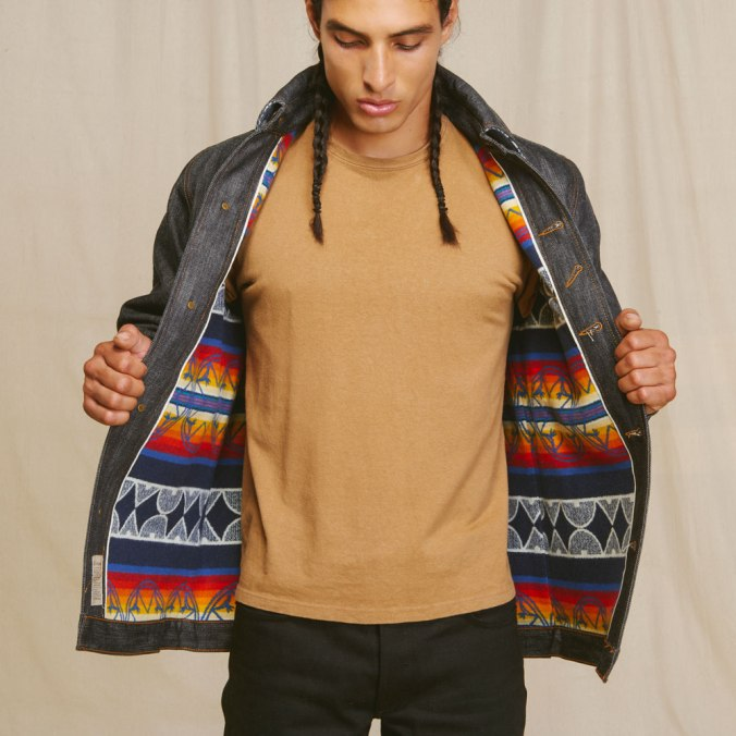 Native American man wearing Ginew denim jacket lined with colorful Paendleton wool - jacket open to show lining