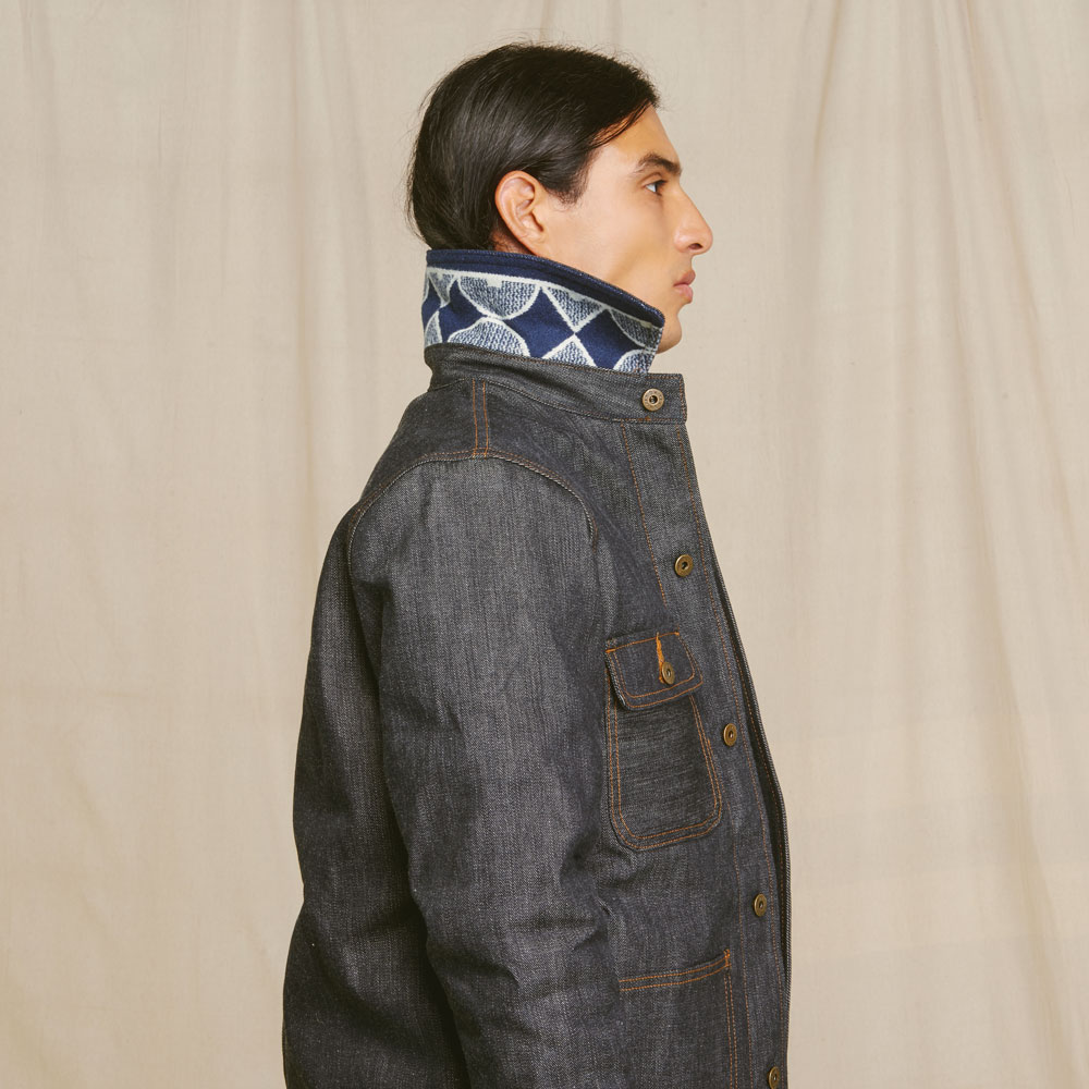 A Native American model stands in profile, wearing a Ginew jacket with the collar turned up to show that the under-collar is lined in Pendleton patterned wool.