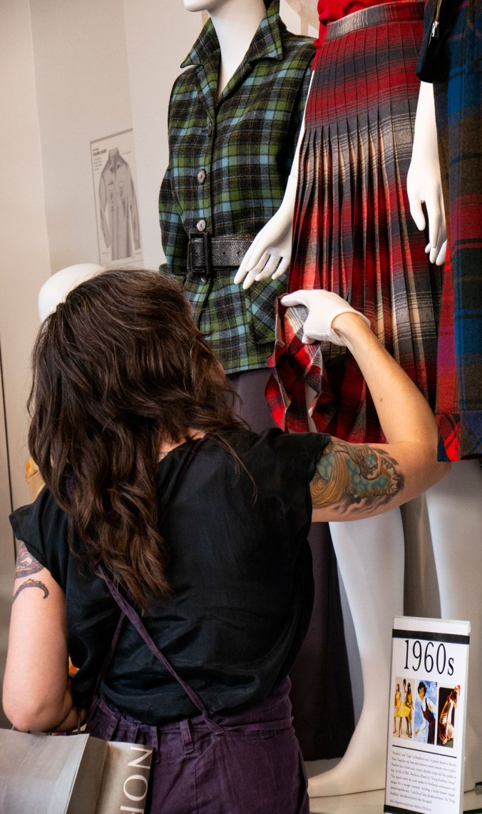 customer in Pendleton store wearing white gloves as she inspects the hem of a Pendleton vintage skirt