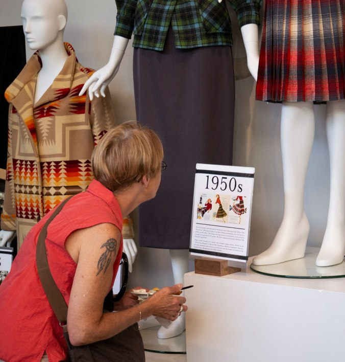 customer in Pendleton store reading placard describing pendleton vintage clothing