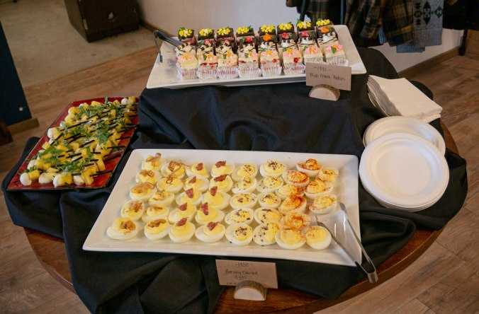 refreshments at party in Pendleton store: deviled eggs, petit fours, fruit skewers, paper plates, serving tongs