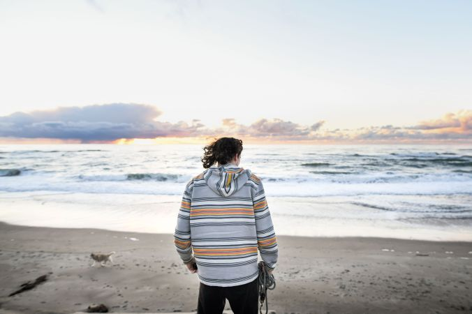 Man standing on beach wearing striped overshirt.