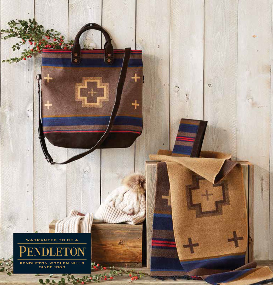 Pendleton bag, scar and hat sitting on a wooden table against a shiplap background.