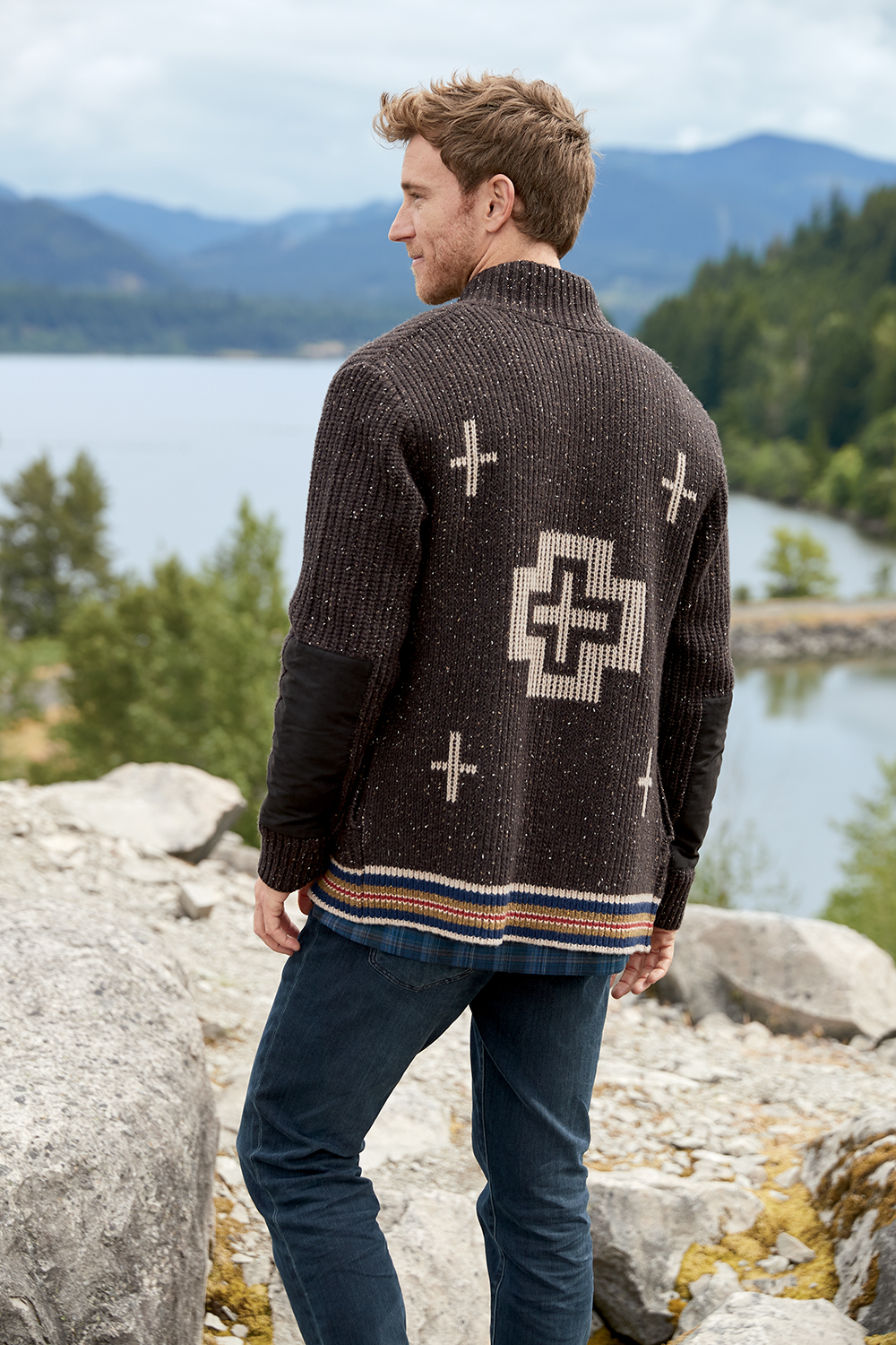 man wearing brown pendleton cardigan standing in front of lake