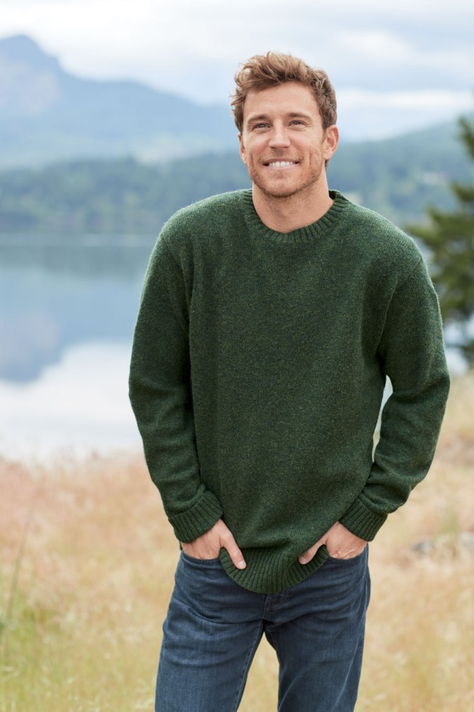 Man wearing green pendleton Shetland wool sweater stands in front of lake